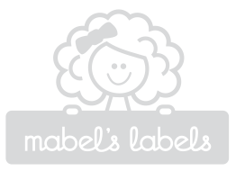 A group of children smiling by a bus.